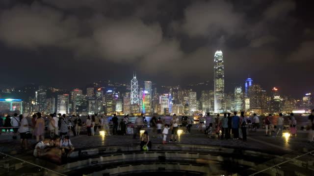 tourists watch the world famous sound and light show along the hong kong skyline. - besichtigung stock-videos und b-roll-filmmaterial