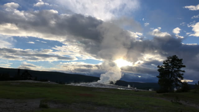 Tourists watching geyser eruption at Sunset