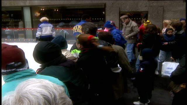tourists watching ice skaters at rockefeller center - ロックフェラーセンターのクリスマスツリー点の映像素材/bロール