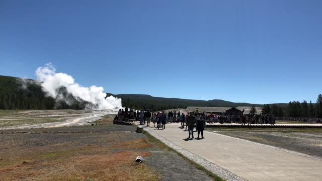 vídeos y material grabado en eventos de stock de tourists watching old faithful geyser eruption - punto de referencia natural