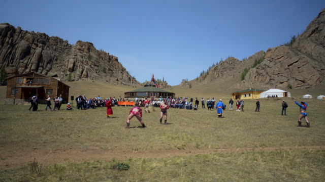 tourists watching wrestlers fighting during naadam against rocky mountains on sunny day - ulaanbaatar, mongolia - 遊牧民族点の映像素材/bロール