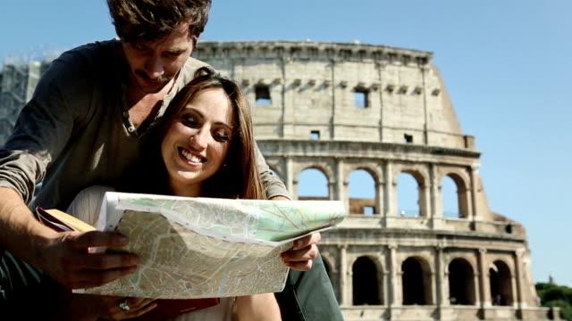 i turisti con guida e mappa davanti al colosseo - indicare la via video stock e b–roll