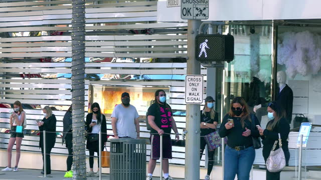 tourists with masks waiting to enter louis vuitton luxury boutique shop on rodeo drive during coronavirus covid-19 pandemic in beverly hills, los angeles, california, 4k - city of los angeles stock videos & royalty-free footage