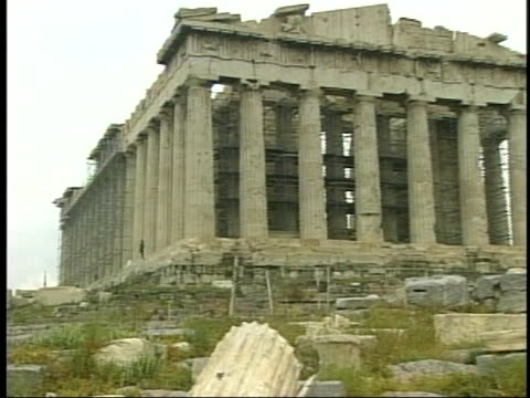 tourists with umbrellas walk among the temples atop the acropolis including the parthenon - ペディメント点の映像素材/bロール