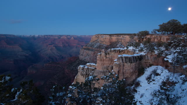 Tovar Hotel overlook on the South Rim of the Grand Canyon (Arizona, USA) featuring the moon rising over the horizon with light snow covering the ground.