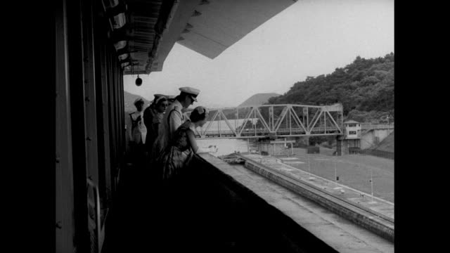 tow car moves along bank of miraflores lock in the panama canal zone / side view queen elizabeth ii and prince philip watch; prince salutes / tow car... - panamakanalen bildbanksvideor och videomaterial från bakom kulisserna