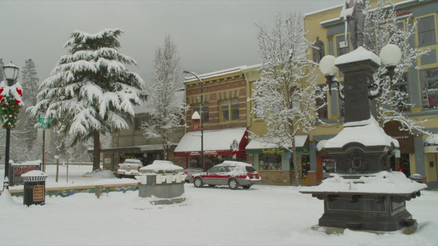 MEDIUM PAN tow cars and one person on snowy street in downtown Ashland, Oregon