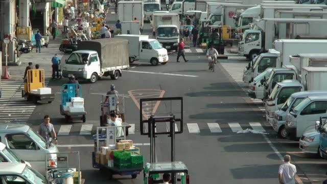 Tow motors and trucks speed through the Tsukiji Market.