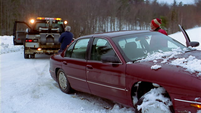 a tow truck driver prepares to rescue a car stuck in a snowbank. - tow truck driver stock videos and b-roll footage