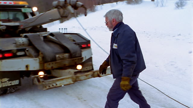 a tow truck driver walks toward his truck in the snow. - tow truck stock videos and b-roll footage