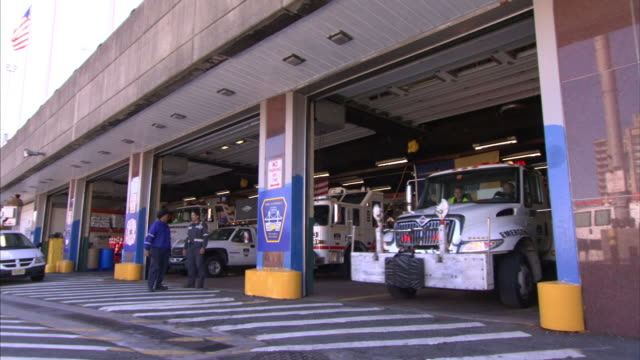 a tow truck exits a garage. - tow truck stock videos and b-roll footage