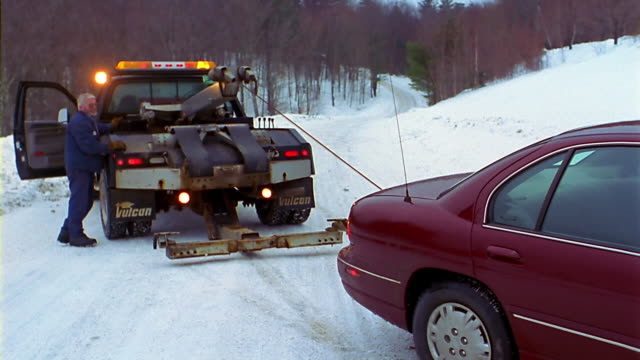 a tow truck pulls a car on a snowy country road. - pulling stock videos & royalty-free footage