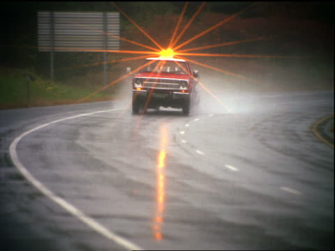 tow truck with flashing light towing car rounding curve on highway in rain - tow truck stock videos and b-roll footage