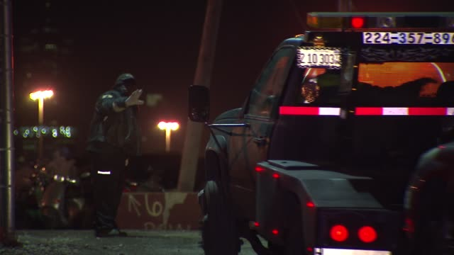 Tow trucks tow cars into lot in Chicago on Dec 1 2014