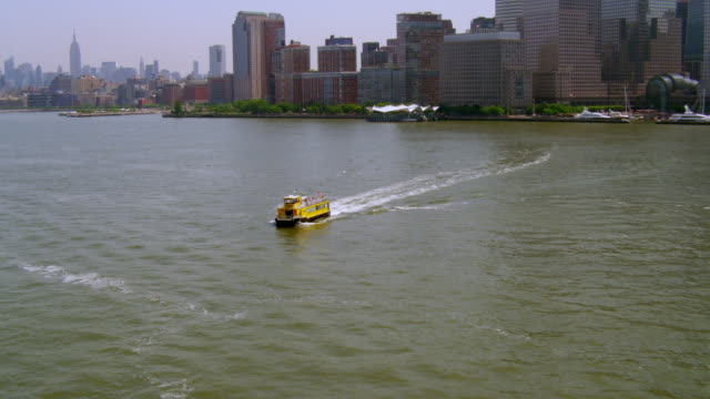 AERIAL POV toward and over small ferry boat in Hudson River with Lower Manhattan in background
