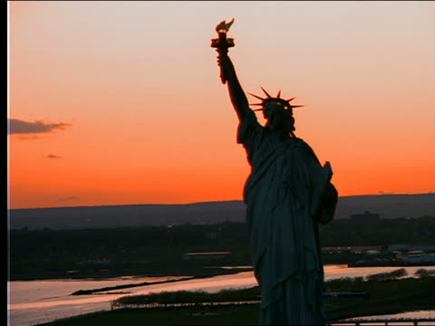 aerial toward + over statue of liberty at sunset - weibliche figur stock-videos und b-roll-filmmaterial