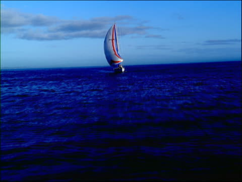 aerial toward + past sailboat with full sails on ocean / ship in background - 船の一部点の映像素材/bロール