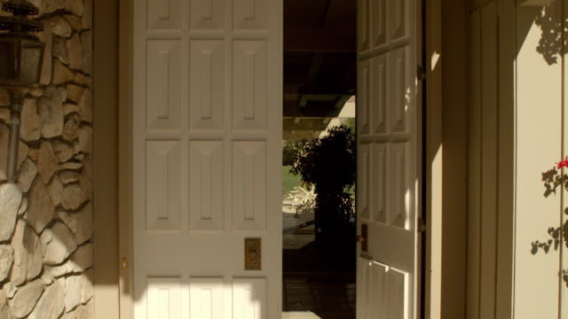 vídeos de stock, filmes e b-roll de pov ds towards large paneled entry doors of mid-century modern home as one of the doors swings open - entrada