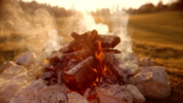 slo mo towards the campfire at sunset - bonfire stock videos & royalty-free footage