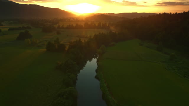 aerial towards the sun rising above the meadows with a river running across them - spring flowing water stock videos & royalty-free footage