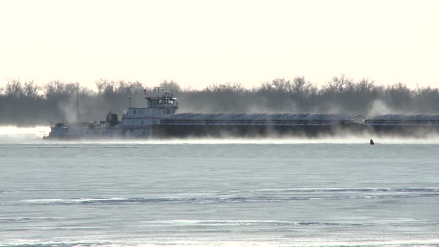 Towboat pushes barges through ice and snow on frozen Mississippi River near coal power plant Arctic temperatures from Winter Storm Ion paralyze US...
