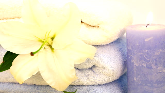Towels, candles and white flower.