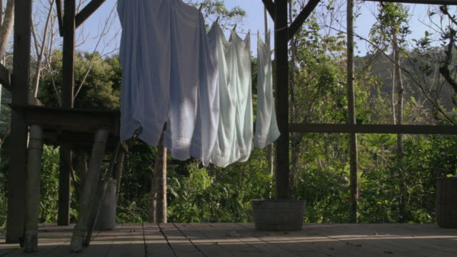 vídeos de stock e filmes b-roll de ms towels hung out to dry on a clothesline strung across a porch / hawaii, united states - toalha