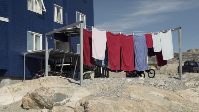 vídeos y material grabado en eventos de stock de towels on a line sway in the breeze obscuring a woman and child as they hang clothes to dry - disko bay, greenland - estar colgado