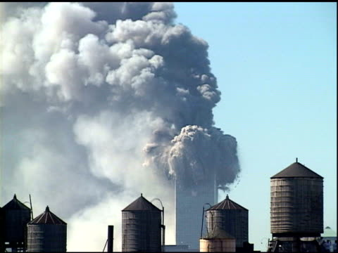 stockvideo's en b-roll-footage met tower 1 burning 15 seconds before collapse building water supply tanks in fg tower 1 collapses in cloud of billowing smoke zo downtown manhattan... - aanslagen op 11 september 2001