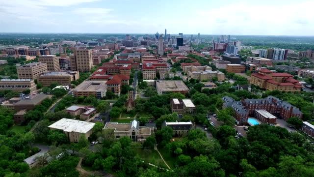 """UT Turm Luftbild Fliegen """" von Austin, Texas, in der Nähe der Universität der Texas bei Austin, Hauptstadt mit Innenstadt Stadtansicht Skyline im Hintergrund in Bewegung nach vorn in der Mitte mit Schwimmbad und die beeindruckende Architektur und die Kirche im Blick"""