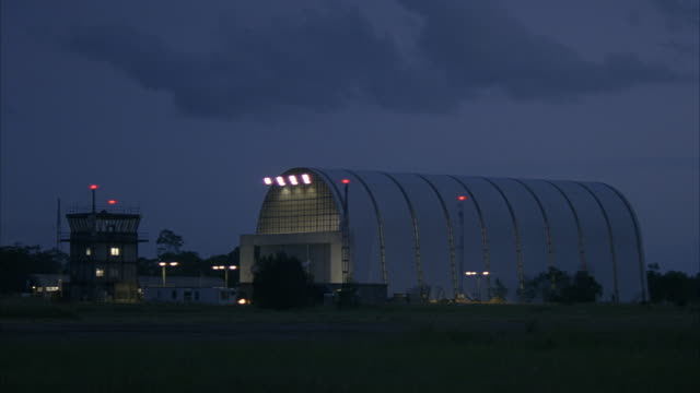 a tower and a hangar stand near a runway at a small airport. - 飛行機格納庫点の映像素材/bロール