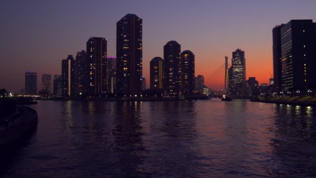 夕暮れ時のタワーアパートメント、隅田川、東京 - 運河点の映像素材/bロール