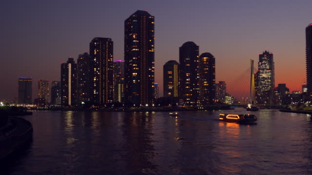 tower apartment at dusk, sumida river, tokyo - riverbank stock videos & royalty-free footage