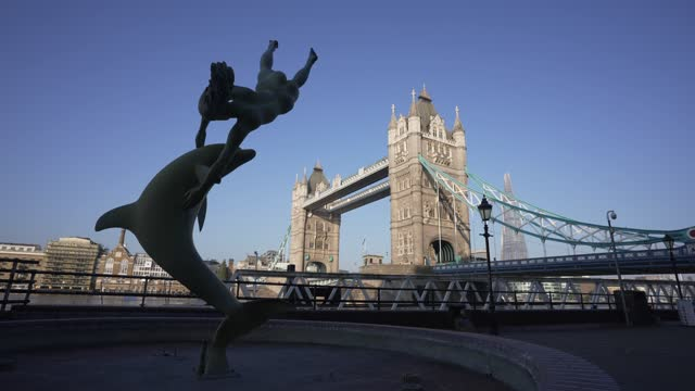 tower bridge and girl with a dolphin statue during early morning, london, england, united kingdom, europe - cetacea stock videos & royalty-free footage