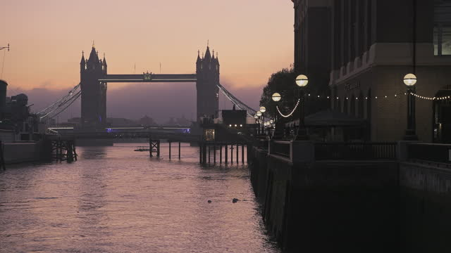 tower bridge and hms belfast in london with beautiful colourful sunrise and orange sky, showing iconic skyline on day one of coronavirus covid-19 lockdown in england, uk - british military stock videos & royalty-free footage
