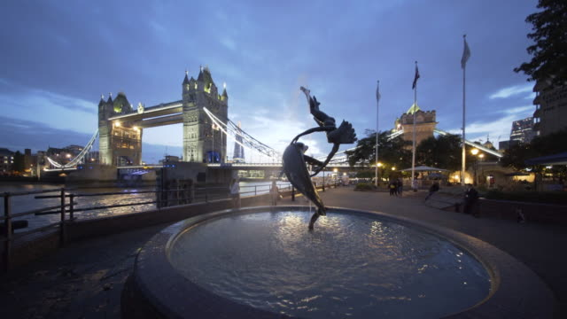tower bridge and the girl with dolphin sculpture at dusk, london, uk - 人の姿点の映像素材/bロール