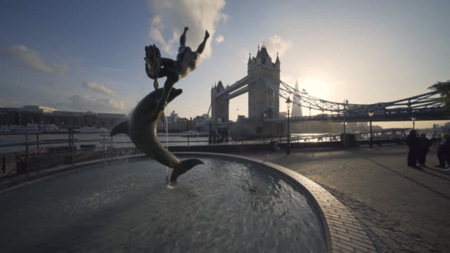 tower bridge and the girl with dolphin sculpture in afternoon sunlight, london, uk - sculpture stock videos & royalty-free footage