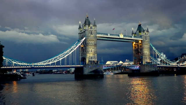 Tower bridge in London at nightfall in a very cloudy day.