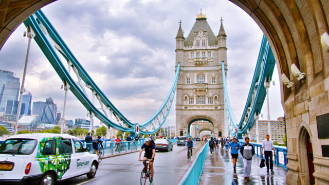 vidéos et rushes de tower bridge à londres. les cyclistes, les voitures, les piétons profitent de la journée - london bridge angleterre
