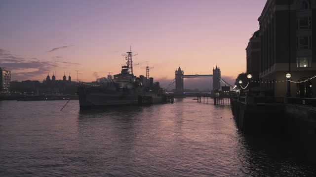 tower bridge in london with beautiful colourful sunrise and purple orange sky, showing iconic skyline and hms belfast on day one of coronavirus covid-19 lockdown in england, uk - british military stock videos & royalty-free footage