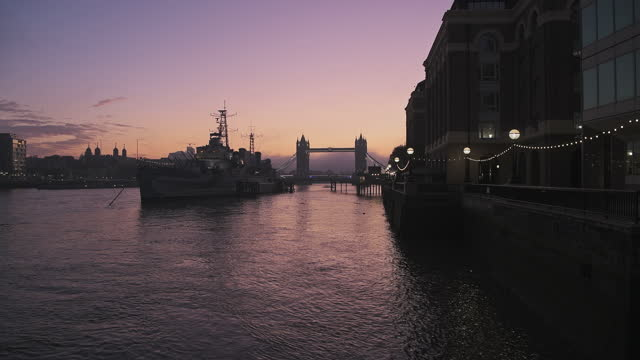 tower bridge in london with beautiful colourful sunrise, dramatic clouds and purple sky, showing iconic famous skyline and hms belfast on day one of coronavirus covid-19 lockdown in england, uk - british military stock videos & royalty-free footage