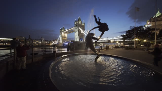 tower bridge opening at night with the girl with dolphin sculpture. - city von london stock-videos und b-roll-filmmaterial