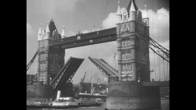 vídeos de stock, filmes e b-roll de tower bridge with its drawbridge raised ship passing underneath then drawbridge starting to close / note exact year not known - drawbridge
