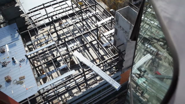 tower crane lifting steel panels at construction site - girder stock videos & royalty-free footage