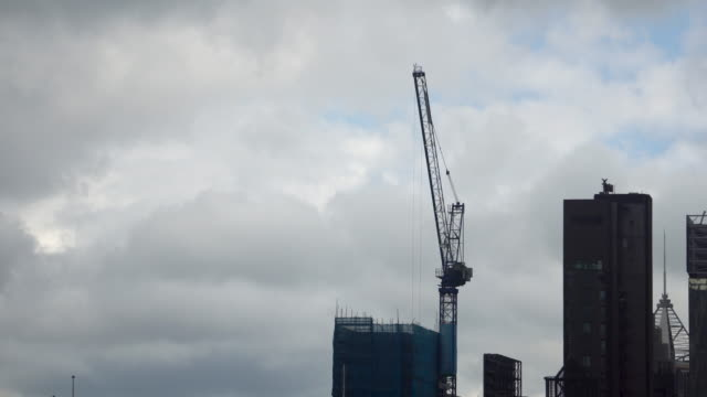 tower crane moving window glass building facade elements bright sky - crane stock videos & royalty-free footage