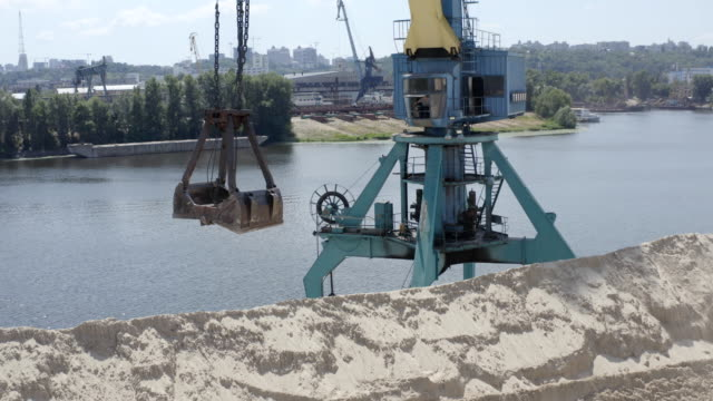 tower cranes loading sand in river port - crane construction machinery stock videos & royalty-free footage