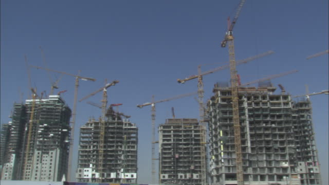 tower cranes stand atop skyscrapers under construction. - real estate stock videos & royalty-free footage