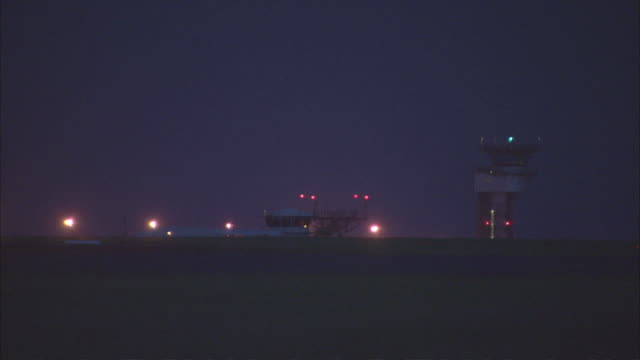 ws tower light rotating in the night sky at an empty airport / darwin, northern territory, australia - stationary process plate stock videos and b-roll footage