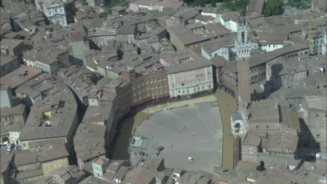 a tower rises above piazza del campo in siena, italy. - piazza del campo stock videos and b-roll footage