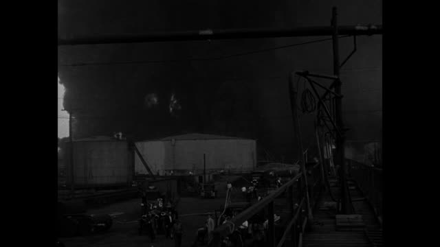 vídeos de stock, filmes e b-roll de towering cloud of smoke in the distance / fire rises through smoke behind large tanks with photographer perched on an array of pipes / vs inky smoke... - cilindro veículo terrestre comercial